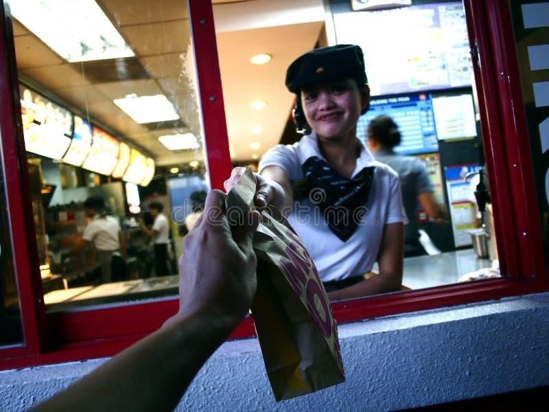 Um trabalhador da cadeia alimentar de fast food dá a um cliente um produto comprado em uma movimentação completamente fotos de stock
