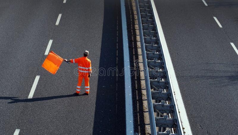 Um trabalhador da estrada com um terno alto do trabalho da visibilidade acena a bandeira alaranjada para retardar o tráfego antes imagens de stock