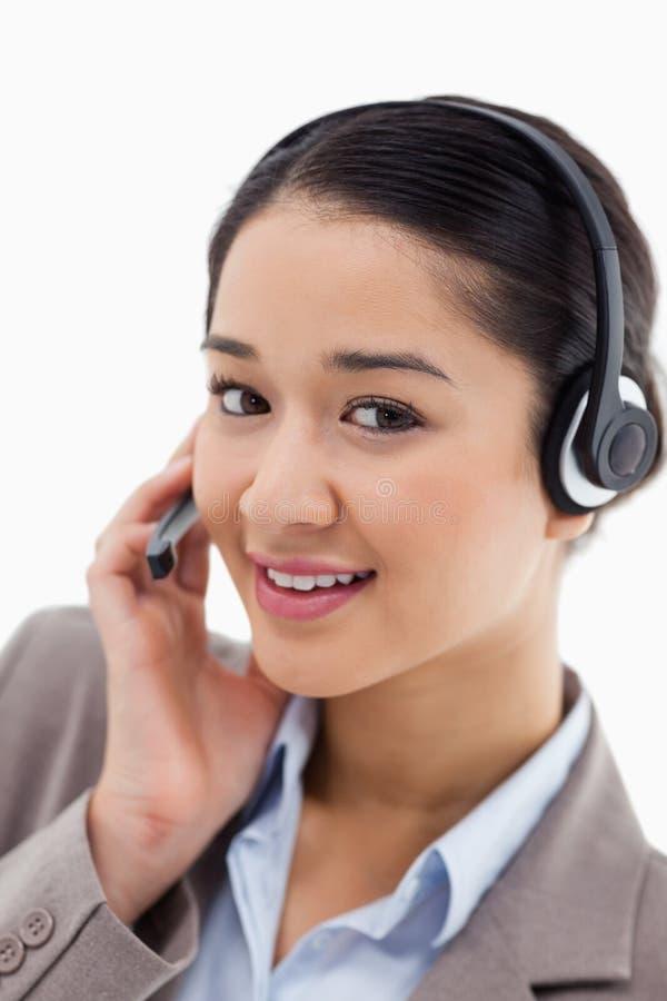 Um trabalhador de escritório bonito que levanta com uns auriculares fotografia de stock royalty free
