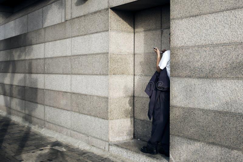 Um trabalhador de escritório toma um resto na esquina da rua imagem de stock royalty free