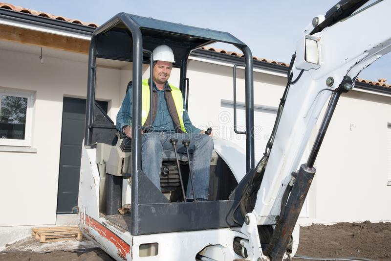 um trabalhador do homem da construção que opera uma máquina da enxada da trilha fotografia de stock royalty free