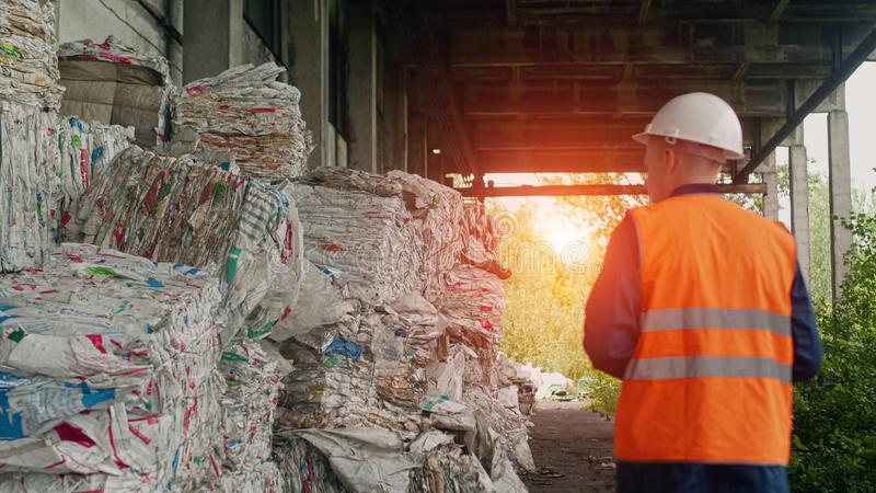 Um trabalhador em uma veste do sinal verifica a quantidade de lixo pressionado e reciclado, reciclagem de resíduos fotos de stock royalty free