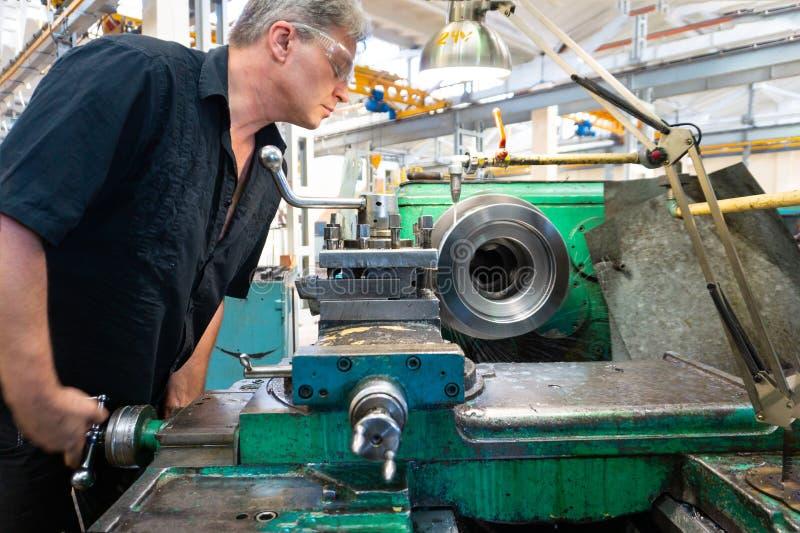Um trabalhador, um homem em uma camisa preta e óculos de proteção, controles uma máquina mecânica Trabalho de giro na produção imagem de stock royalty free