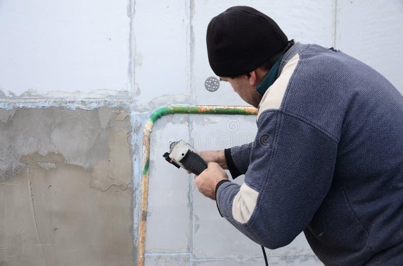 Um trabalhador idoso fura um furo em uma parede do isopor para a instalação subsequente de um passador de reforço plástico imagens de stock royalty free