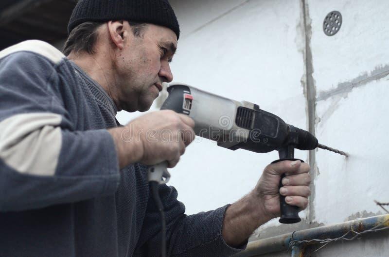 Um trabalhador idoso fura um furo em uma parede do isopor para a instalação subsequente de um passador de reforço plástico fotografia de stock