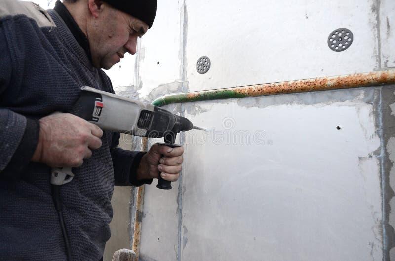Um trabalhador idoso fura um furo em uma parede do isopor para a instalação subsequente de um passador de reforço plástico imagens de stock