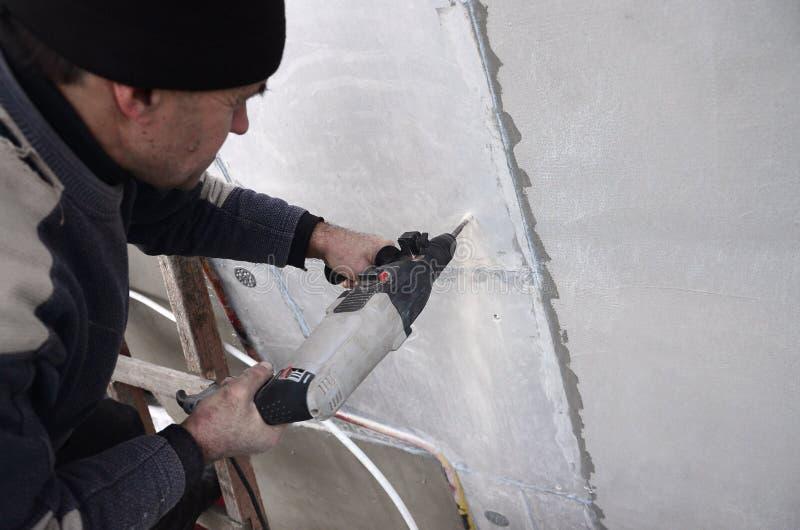 Um trabalhador idoso fura um furo em uma parede do isopor para a instalação subsequente de um passador de reforço plástico imagem de stock royalty free