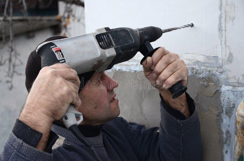 Um trabalhador idoso fura um furo em uma parede do isopor para a instalação subsequente de um passador de reforço plástico foto de stock royalty free