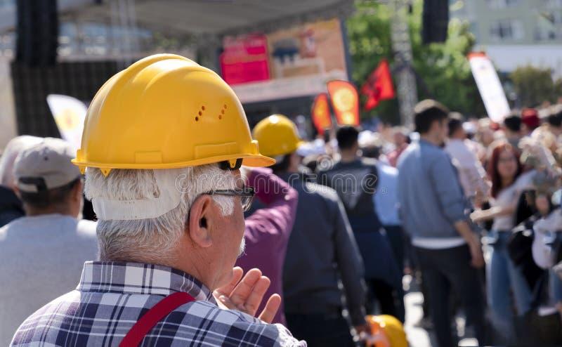 Um trabalhador idoso n?o identificado com capacete amarelo junta-se ao Dia do Trabalhador do 1? de maio fotos de stock