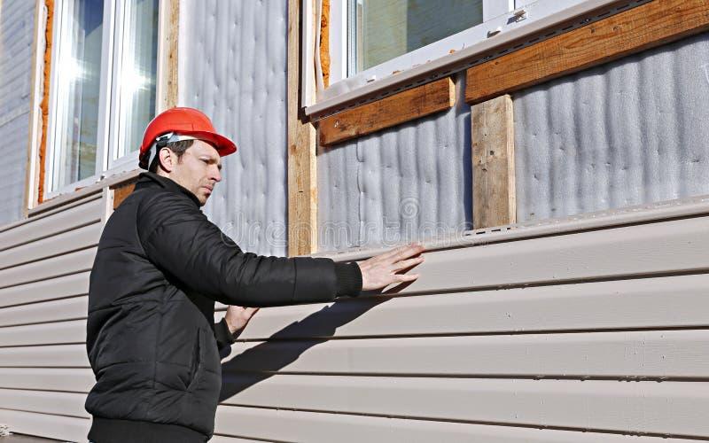 Um trabalhador instala o tapume bege dos painéis na fachada foto de stock