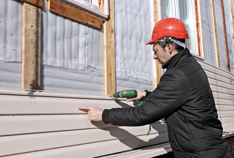 Um trabalhador instala o tapume bege dos painéis na fachada imagem de stock royalty free