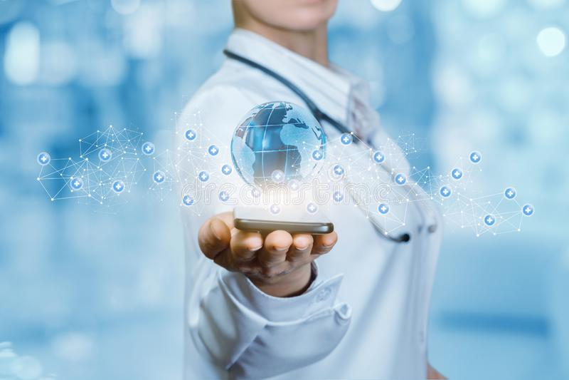 Um trabalhador médico está mantendo um telefone celular com o voo global do mapa acima cercado por moléculas pequenas imagem de stock royalty free