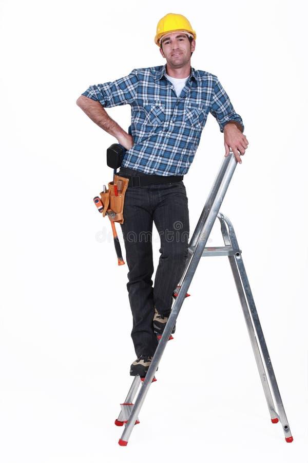 Um trabalhador manual em uma escada. fotos de stock royalty free