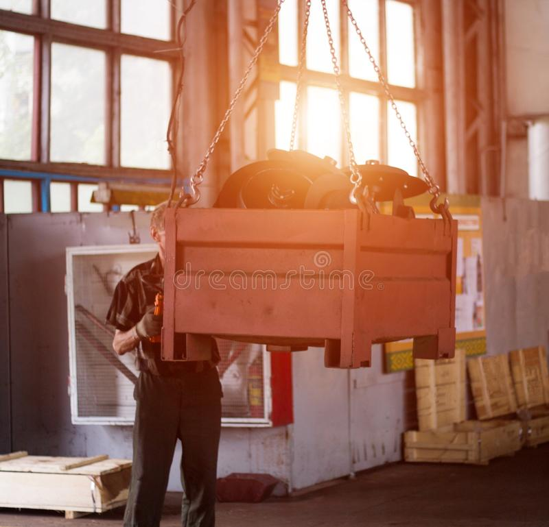 Um trabalhador masculino sem um capacete aumenta o recipiente do metal de um guindaste da produção com um feixe, uma violação de  fotografia de stock royalty free