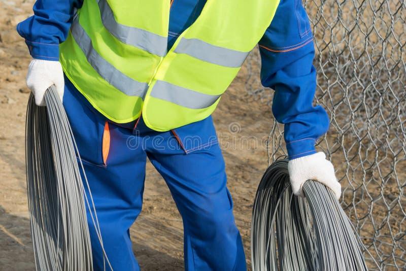 Um trabalhador na roupa da construção leva uma bobina do fio do ferro imagens de stock