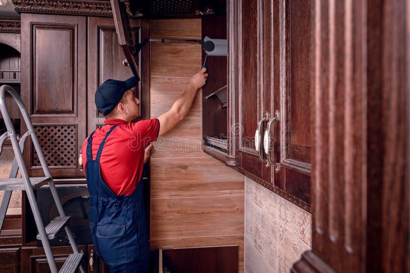 Um trabalhador novo está montando a mobília de madeira moderna da cozinha fotos de stock royalty free
