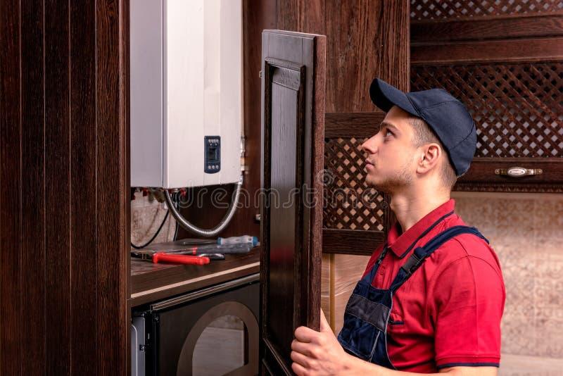 Um trabalhador novo est? montando a mob?lia de madeira moderna da cozinha imagem de stock