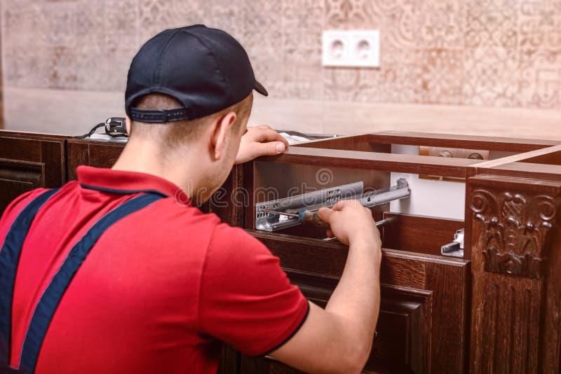 Um trabalhador novo instala uma gaveta A instalação da mobília de madeira moderna da cozinha fotos de stock