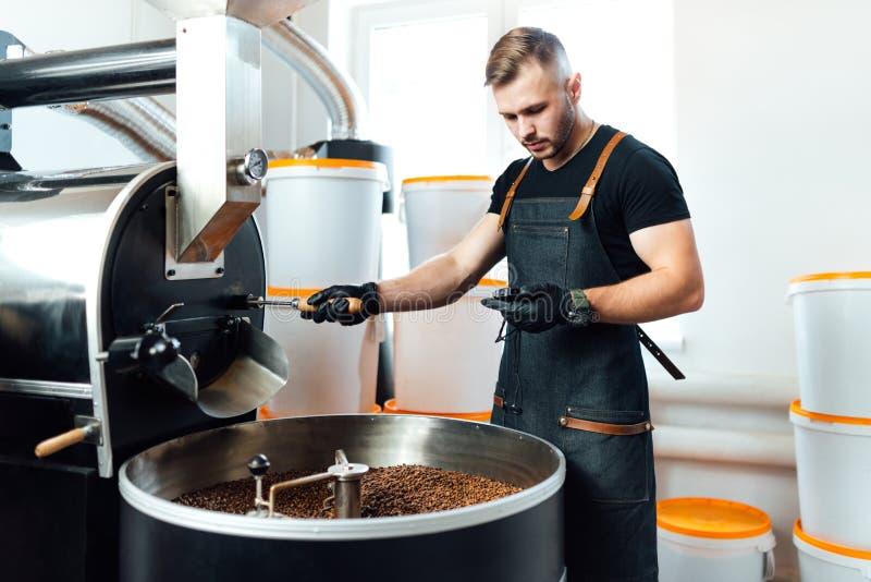 Um trabalhador perto do equipamento de torrefação de café verificará o tempo de teste da amostra imagens de stock