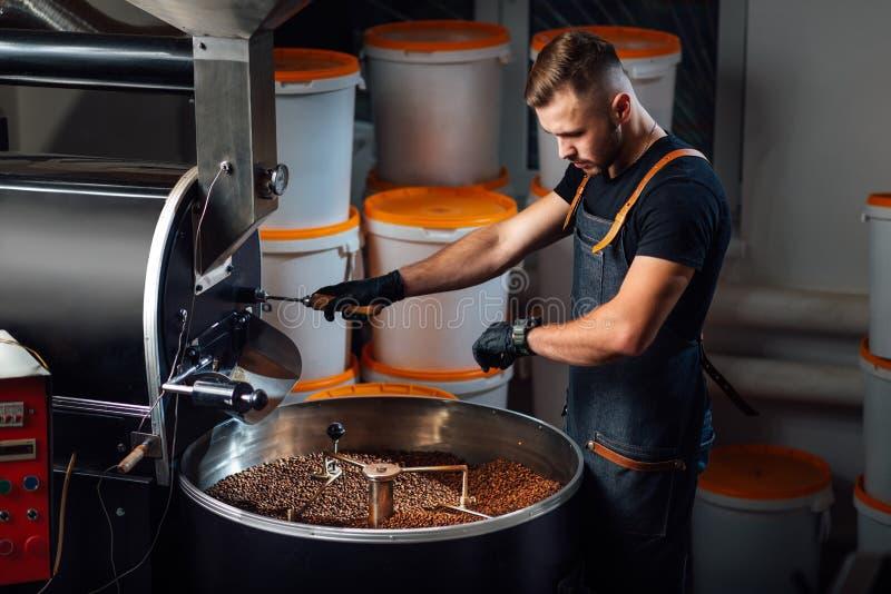 Um trabalhador perto do equipamento de torrefação de café verificará o tempo de teste da amostra foto de stock royalty free