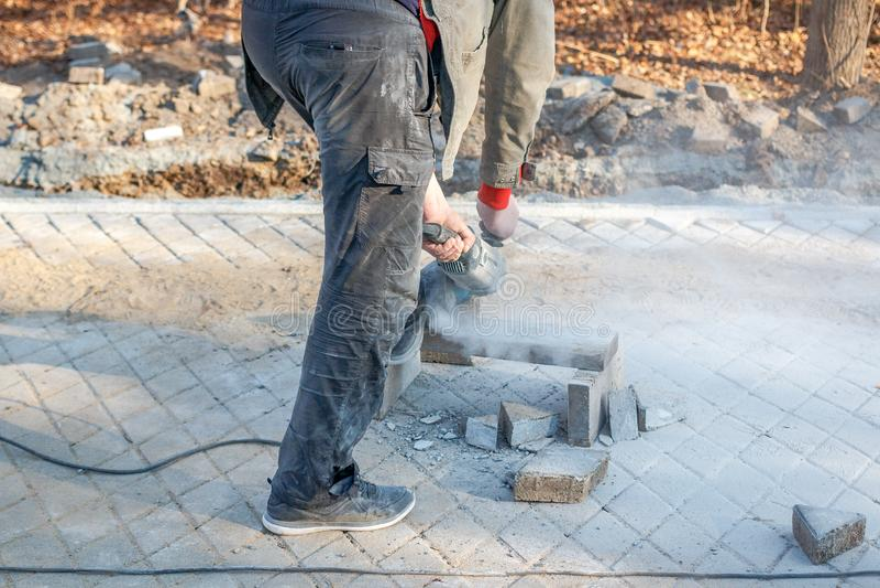 Um trabalhador prepara um passeio pavimentando um passeio fotos de stock
