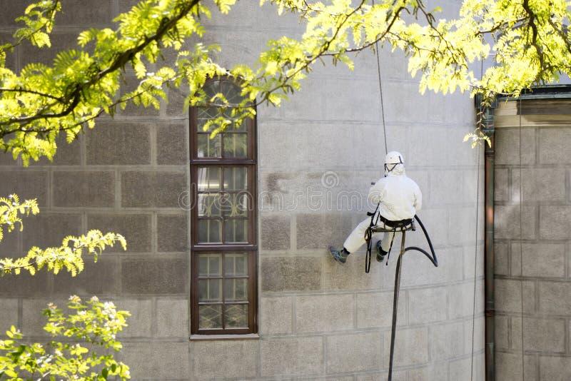 Um trabalhador que veste uma engrenagem protetora que limpa uma fachada de pedra fotografia de stock royalty free