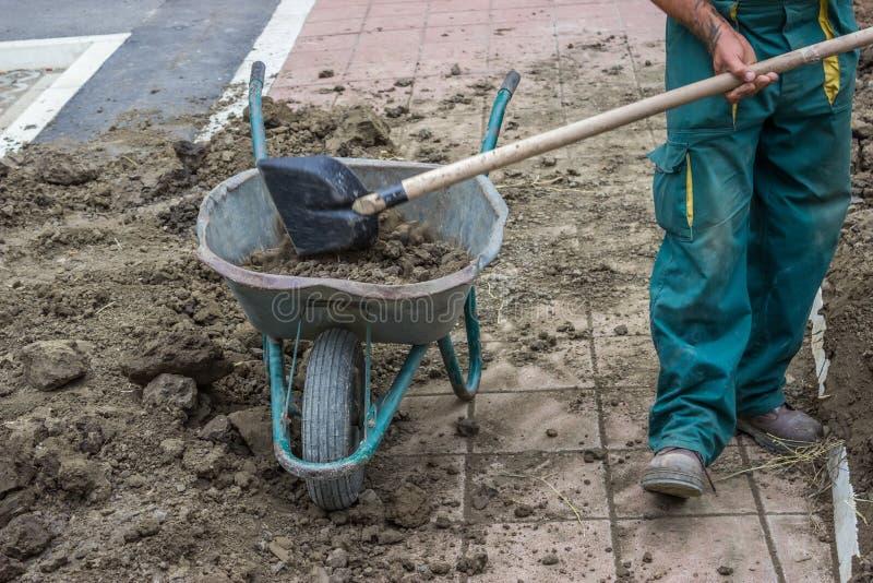 Um trabalhador trabalha com pá a sujeira em um carrinho de mão 3 fotos de stock royalty free