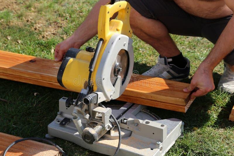 Um trabalhador viu que a madeira com uma costeleta viu fotografia de stock