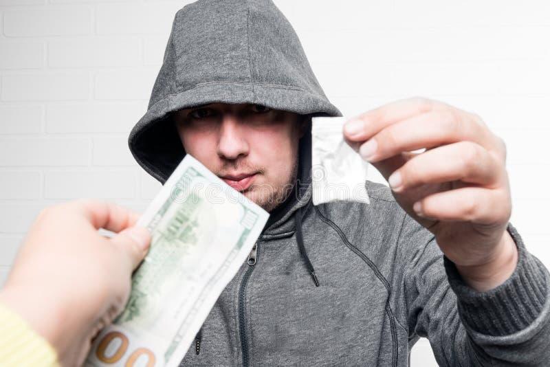 Um traficante de drogas em uma capa vende drogas fotografia de stock royalty free