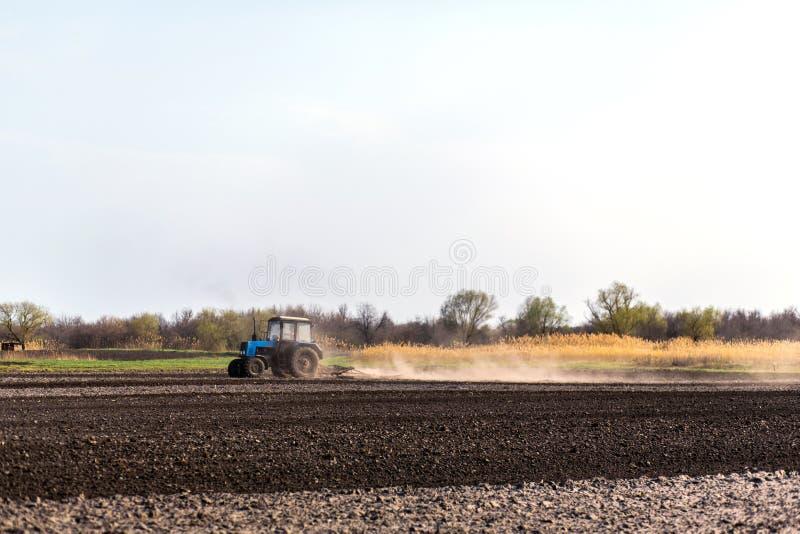 Um trator ara um campo para semear colheitas imagem de stock