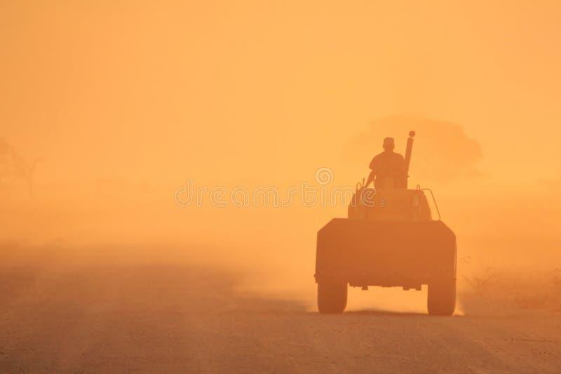 Um trator e seu motorista - fundo dourado do por do sol da poeira, da selva de África fotos de stock