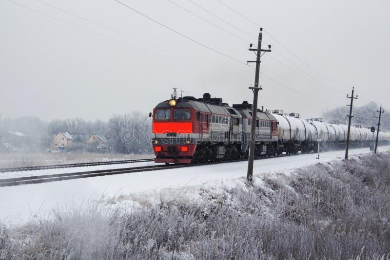 Um trem de mercadorias alaranjado brilhante no movimento no inverno fotos de stock