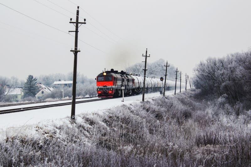Um trem de mercadorias alaranjado brilhante no movimento no inverno imagem de stock