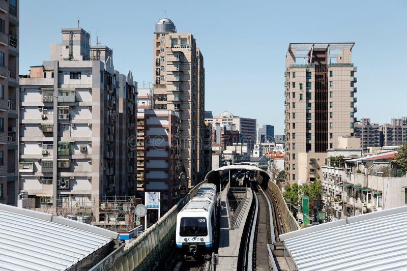 Um trem do metro viaja nos trilhos elevados entre as torres do escritório e os blocos residenciais, chegando em uma estação do si fotos de stock royalty free