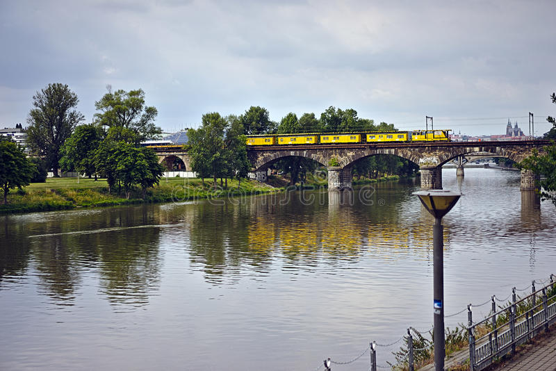 Um trem que cruza uma ponte sobre um rio imagens de stock