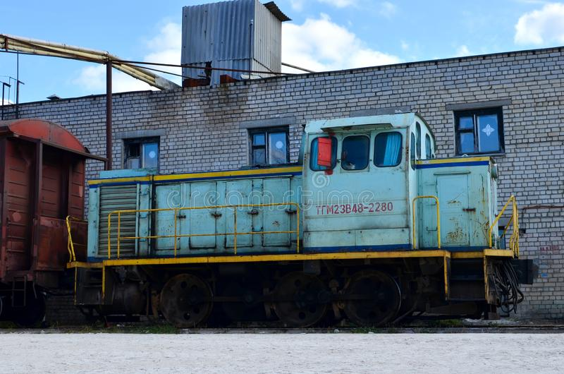 Um trem velho com carros de frete está estando nas trilhas de estrada de ferro na zona retardada fotografia de stock royalty free