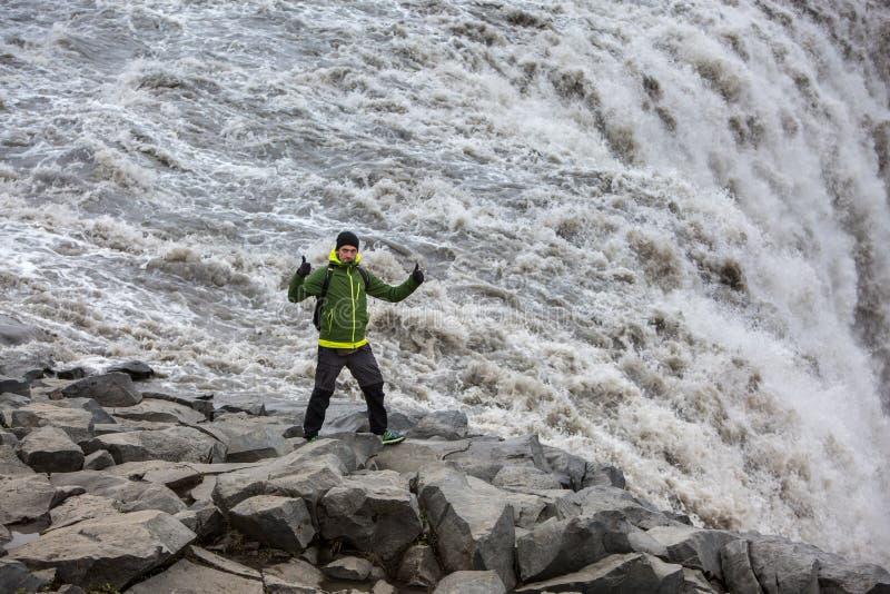 Um turista com uma trouxa anda ao longo da borda mesma da cachoeira poderosa de Dettifoss imagens de stock