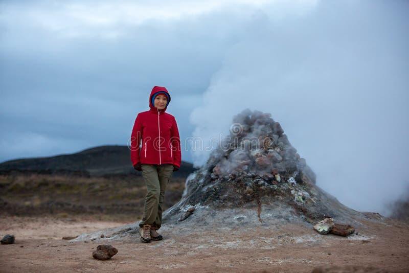 Um turista da menina em um revestimento vermelho está na perspectiva do fumo sulfúrico que entra em erupção da terra imagem de stock royalty free