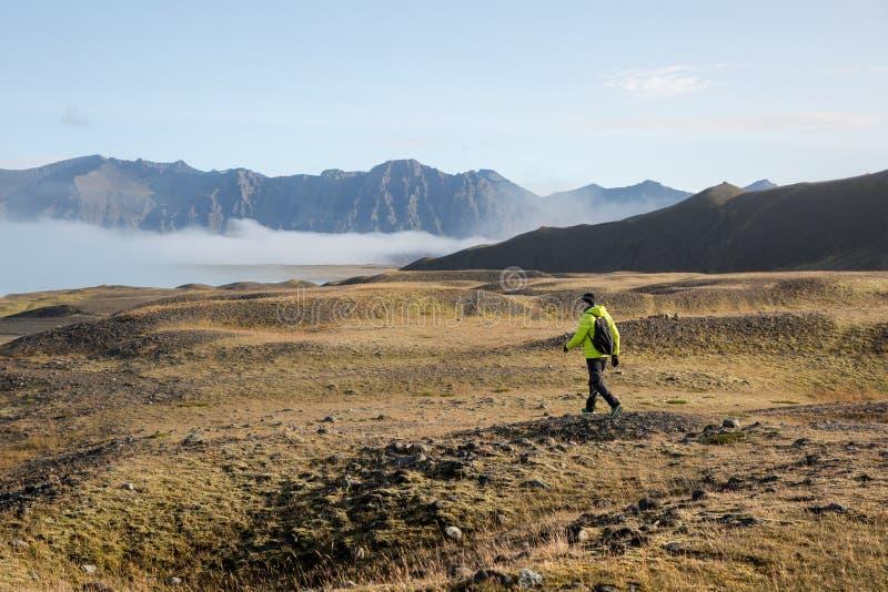 Um turista em um revestimento amarelo anda no alvorecer para as montanhas e a névoa imagem de stock royalty free