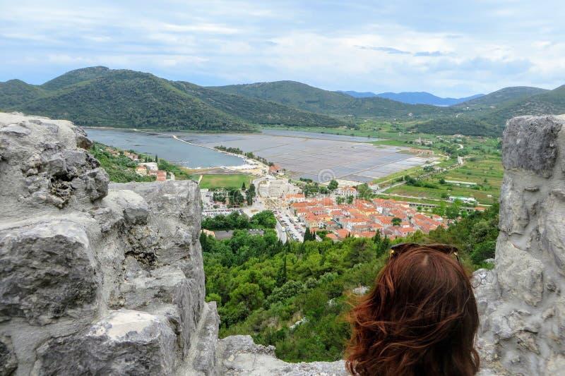 Um turista fêmea novo que admira as vistas da cidade medieval histórica de Ston, Croácia Sua opinião é da elevação acima ao longo imagens de stock