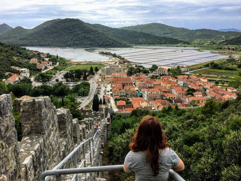 Um turista fêmea novo que admira as vistas da cidade medieval histórica de Ston, Croácia imagens de stock royalty free