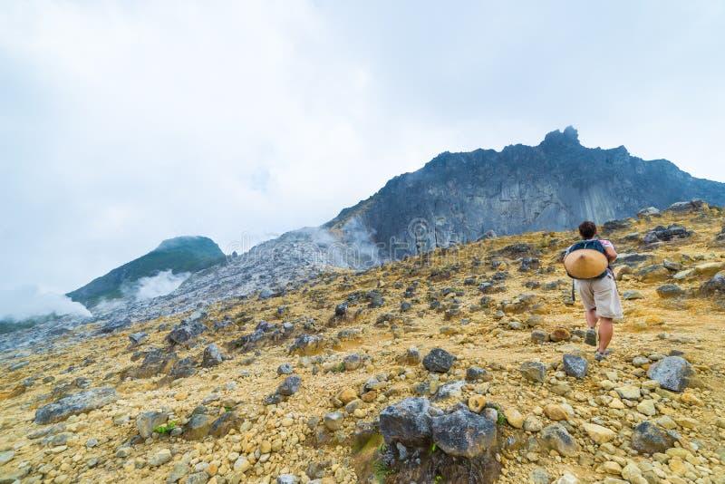 Um turista que escala o vulcão de Sibayak, caldera ativo que cozinha, marco natural do destino famoso do curso em Berastagi Sumat imagens de stock