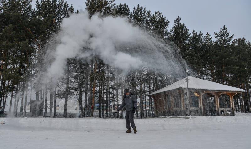 Um turista que joga a ?gua quente no parque do inverno foto de stock