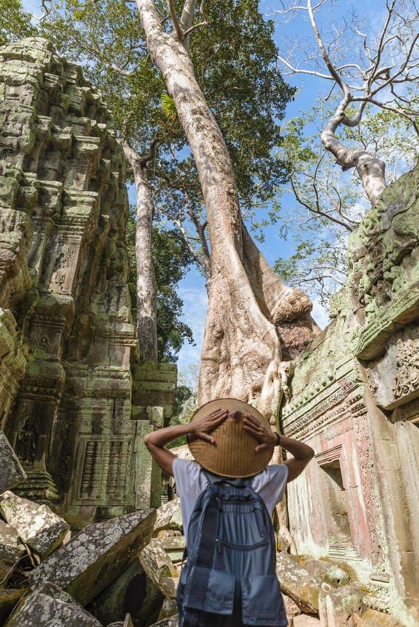 Um turista que visita ruínas de Angkor entre a selva, complexo do templo de Angkor Wat, destino Camboja do curso Mulher com chap imagens de stock royalty free