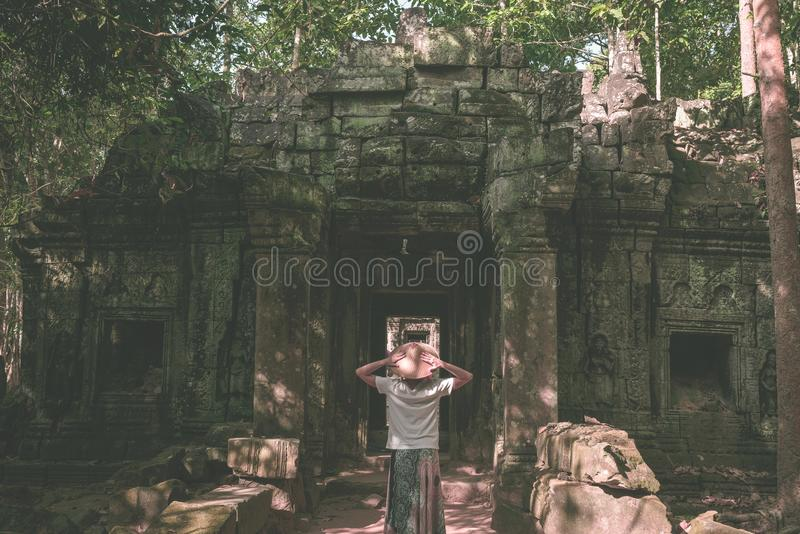 Um turista que visita ruínas de Angkor entre a selva, complexo do templo de Angkor Wat, destino Camboja do curso Mulher com chap imagens de stock