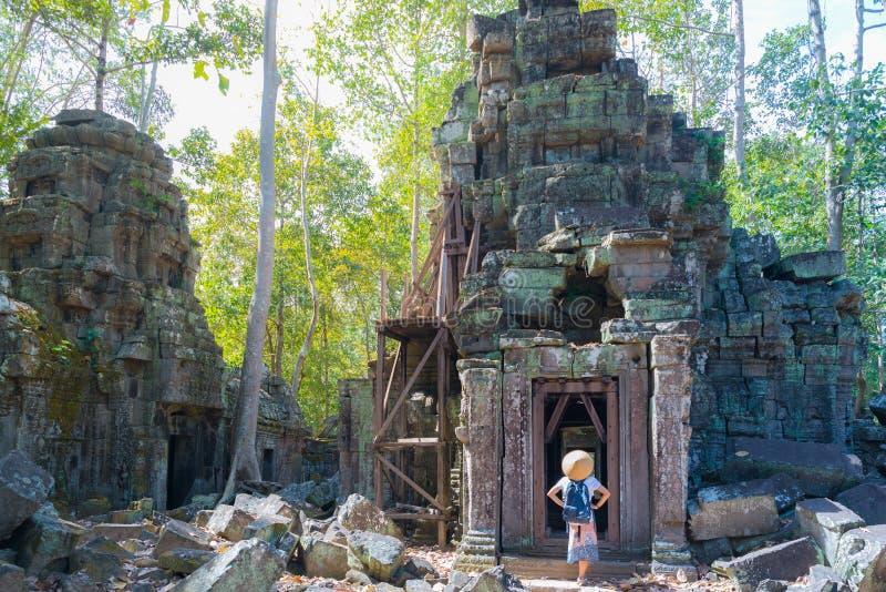 Um turista que visita ruínas de Angkor entre a selva, templo de Ta Nei, destino Camboja do curso Mulher com chapéu tradicional, v foto de stock royalty free