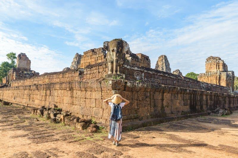 Um turista que visita ruínas de Angkor Wat no nascer do sol, pre templo de Rup, destino Camboja do curso Mulher com chapéu tradic foto de stock royalty free