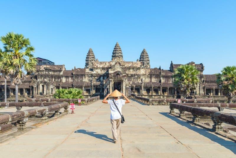 Um turista que visita ru?nas de Angkor Wat no nascer do sol, destino Camboja do curso Mulher com chap?u tradicional e os bra?os a foto de stock