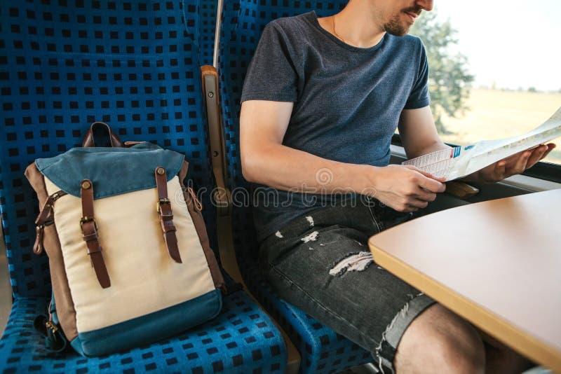 Um turista senta-se pela janela em um trem ou em um trem da periferia e olha-se um mapa imagens de stock