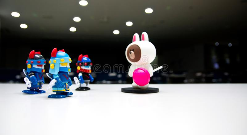 Um urso branco com uns doces cor-de-rosa em uma fase escura do teatro sem uma diz os protetores do robô que vestem capacetes azui imagens de stock